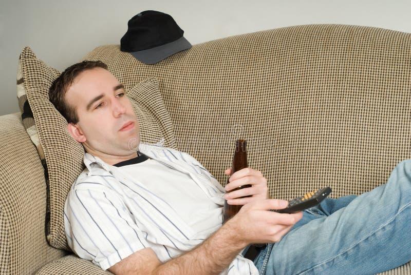 Macho com cerveja que presta atenção à tevê imagens de stock