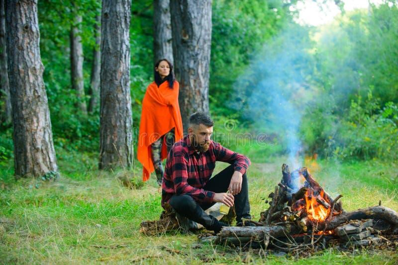 Macho com a cerveja que senta-se perto da fogueira, férias com esposa imagem de stock