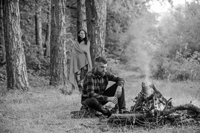 Macho com a cerveja que senta-se perto da fogueira, férias com esposa imagens de stock royalty free