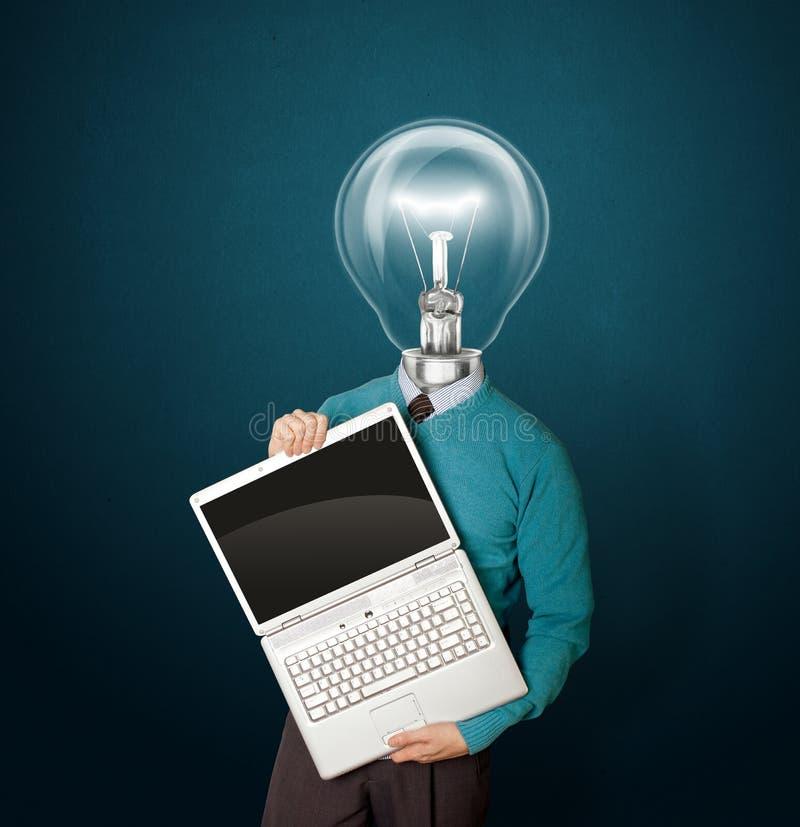 Macho com lâmpada-cabeça no azul com portátil fotografia de stock