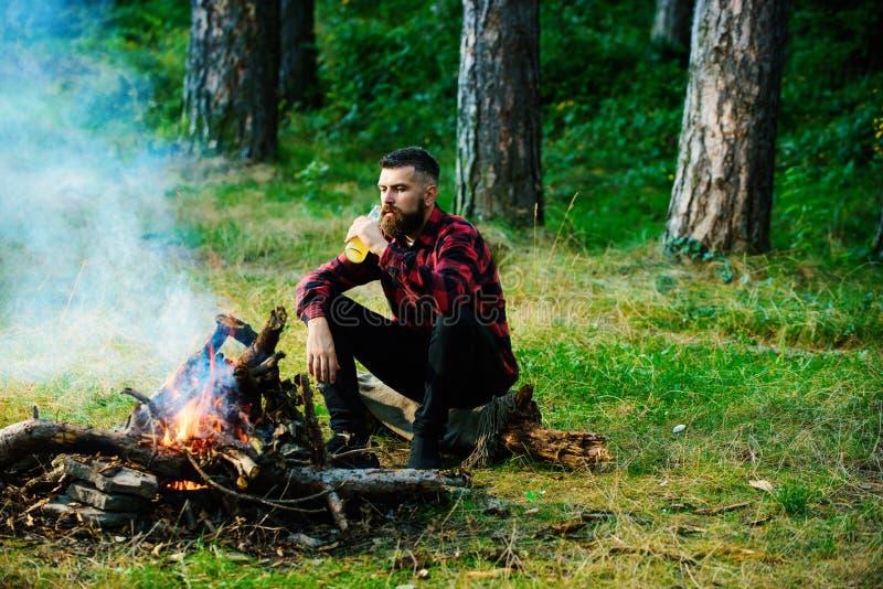 Macho considerável com a cerveja que senta-se perto da fogueira, fotografia de stock royalty free