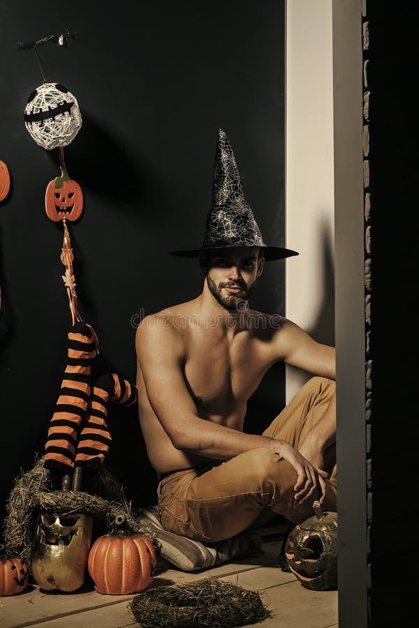 Macho de Halloween dans le chapeau de sorcière et la séance dénudée de torse photographie stock libre de droits
