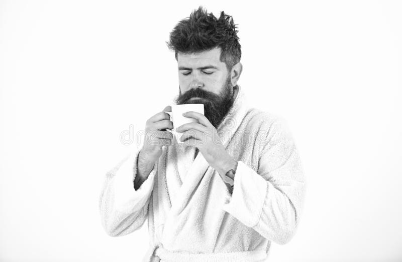 Macho drowsy, sleepy face drinks coffee in morning enjoying aroma. Man with beard and disheveled hair stands in bathrobe stock image