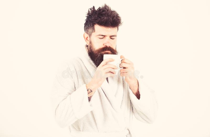 Macho drowsy, sleepy face drinks coffee in morning enjoying aroma. Man with beard and disheveled hair stands in bathrobe royalty free stock photos