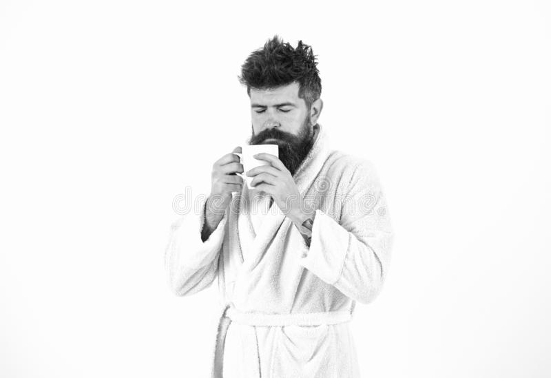 Macho drowsy, sleepy face drinks coffee in morning enjoying aroma. Morning rituals concept. Man with beard and stock images