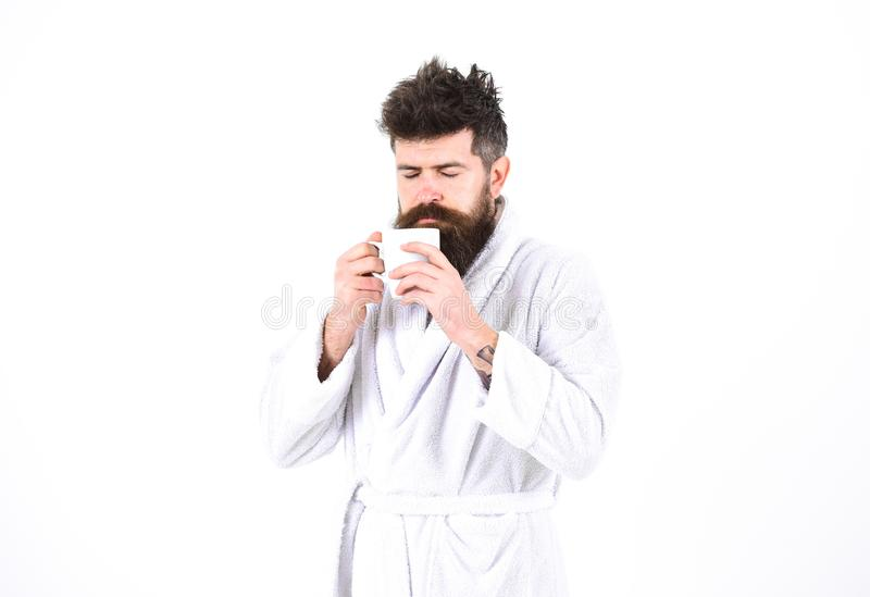 Macho drowsy, sleepy face drinks coffee in morning enjoying aroma. Morning rituals concept. Man with beard and royalty free stock photos