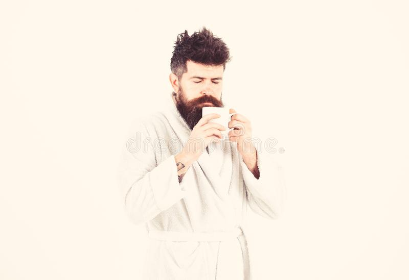 Macho drowsy, sleepy face drinks coffee in morning enjoying aroma. Morning rituals concept. Man with beard and royalty free stock photography