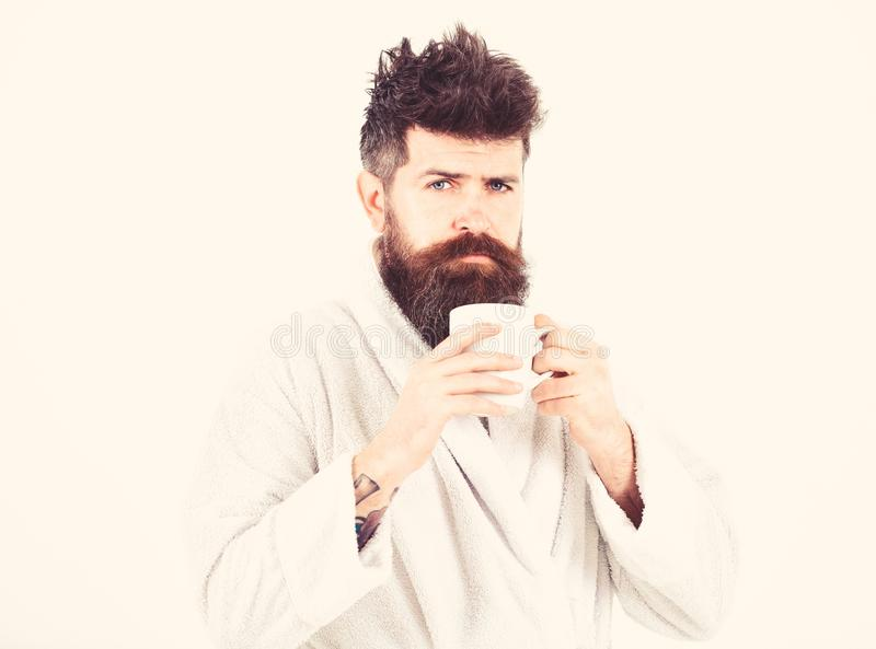 Macho drowsy, sleepy with strict face drinks coffee in morning. Morning rituals concept. Man with beard and disheveled. Hair stands in bathrobe, holds mug with stock images
