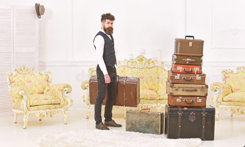 Macho elegancki na surowej twarzy niesie rocznik walizkę Bagaż i przeniesienia pojęcie Mężczyzna, kamerdyner z brodą i fotografia stock