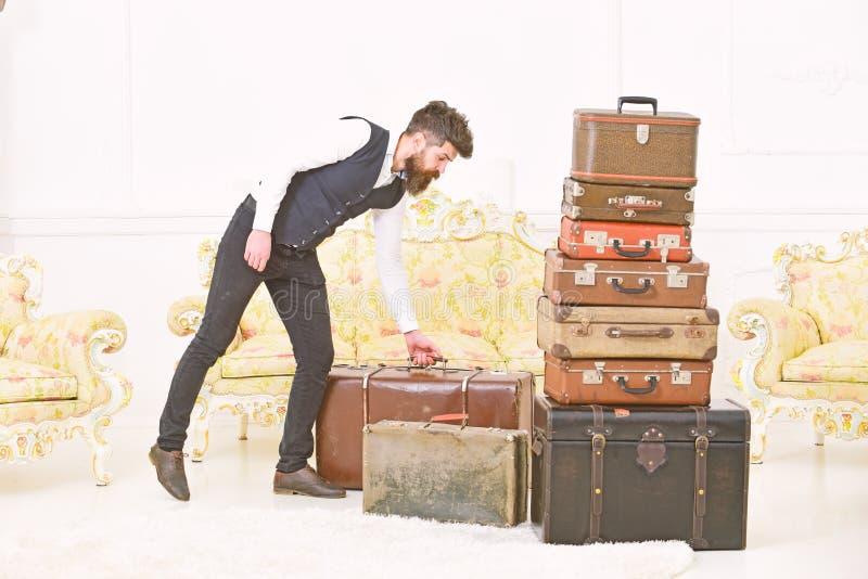 Macho elegancki na surowej twarzy niesie rocznik walizkę Mężczyzna, kamerdyner z brodą i wąsy jest ubranym klasycznego kostium, d zdjęcie royalty free