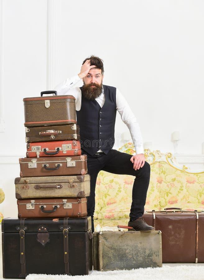 Macho elegant op teleurgesteld gezicht die zich dichtbij stapel van uitstekende koffer bevinden De mens, de butler met baard en d stock foto