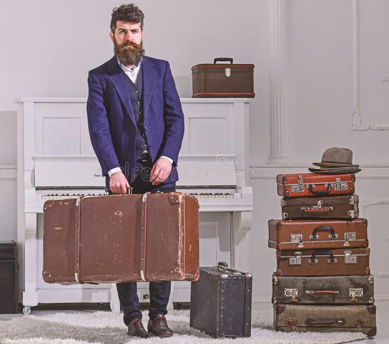 Macho elegant på strikt framsida står nära högen av tappningresväskan, rymmer resväskan Man handelsresande med skägget och royaltyfri fotografi