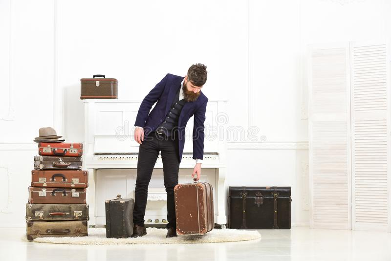 Macho elegant on strict face stands near pile of vintage suitcase, ready for vacation. Man, traveller with beard and royalty free stock photo
