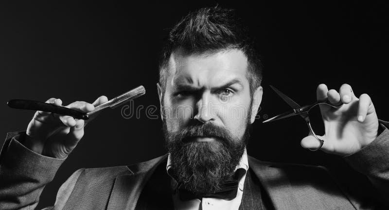 Macho em cortes do terno e barba e bigode formais das barbeações O homem com barba guarda a rapagem da lâmina e das tesouras imagem de stock royalty free
