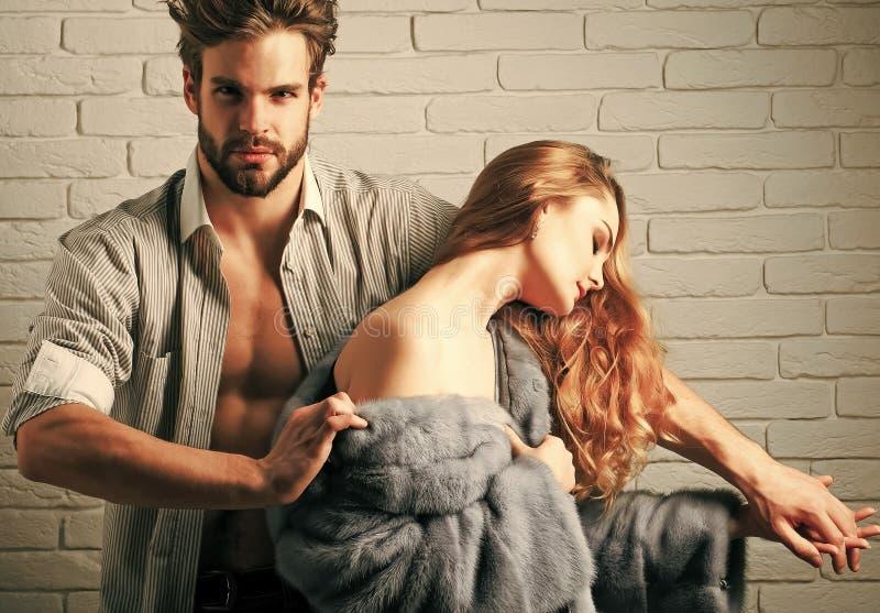 Macho entfernen Pelzmantel vom Mädchen stockbild