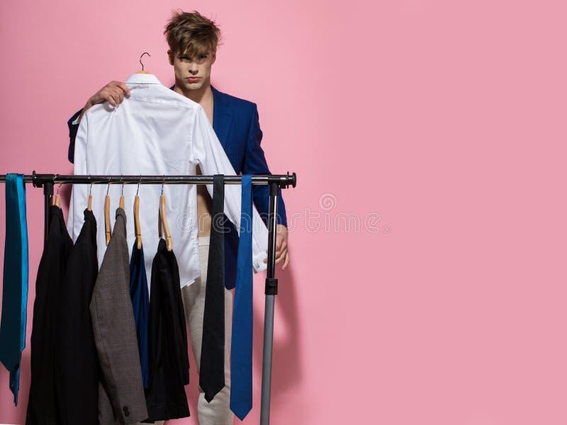 Macho escolha a camisa no vestu?rio no fundo cor-de-rosa imagem de stock royalty free
