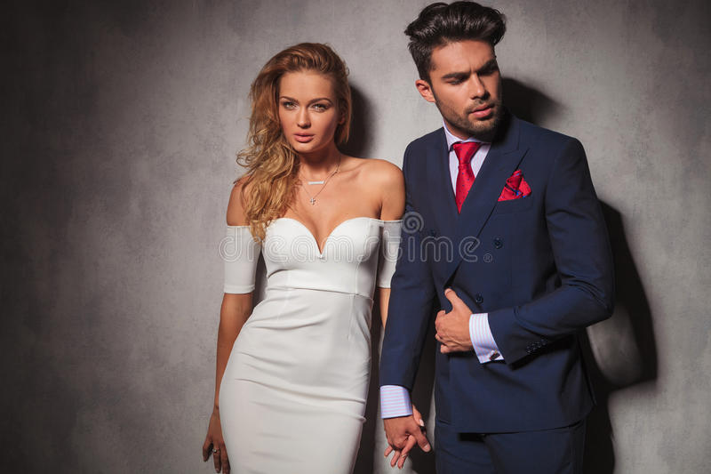 Macho fashion elegant man holding his lover by her hand. Macho fashion elegant men holding his lover by her hand and looks to a side, women is looking at the stock photo