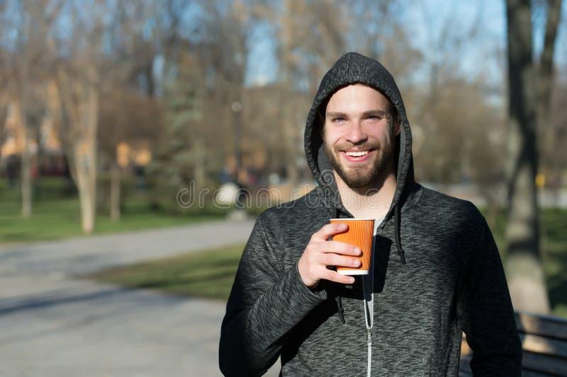 Macho feliz no copo de café descartável da posse da capa no parque ensolarado Sorriso farpado do homem com bebida afastada no ar  fotos de stock royalty free