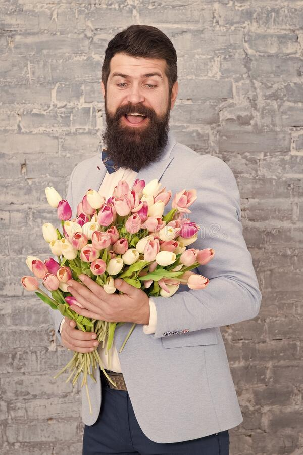 Macho getting ready romantic date. Tulips for sweetheart. Romantic gift. Man well groomed wear blue tuxedo bow tie hold stock image