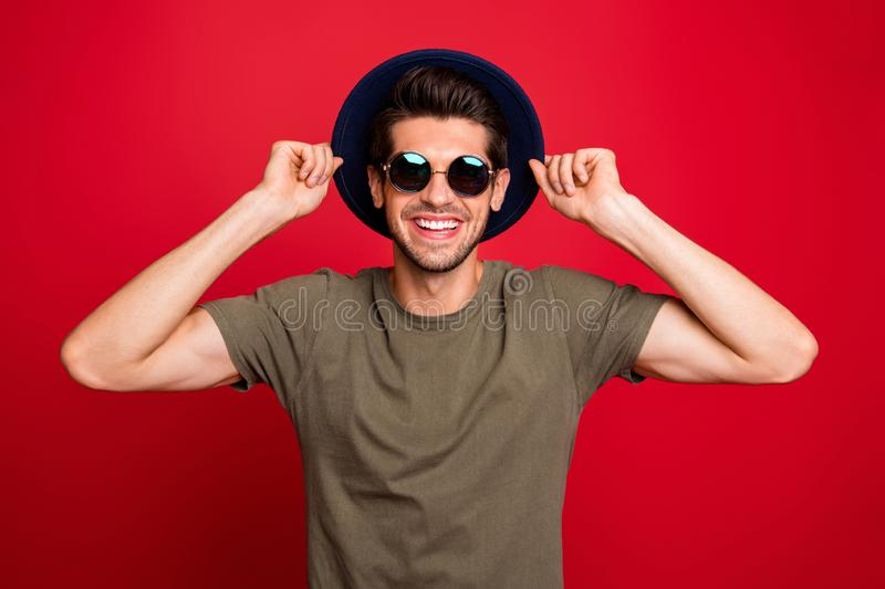 Macho guy holding hands fixing old-fashioned blue hat wear specs grey t-shirt isolated on red background royalty free stock images