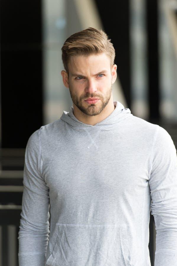 Macho in maglietta felpata all'aperto Uomo barbuto con il fronte serio su aria fresca Presa della rottura minuscola   sporty immagine stock