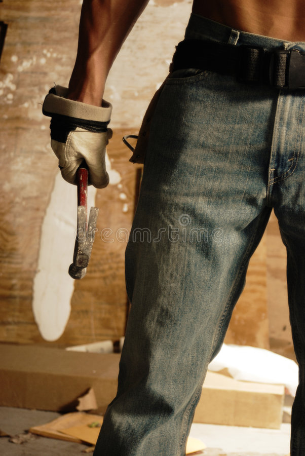 Macho magro nas calças de brim com martelo fotografia de stock
