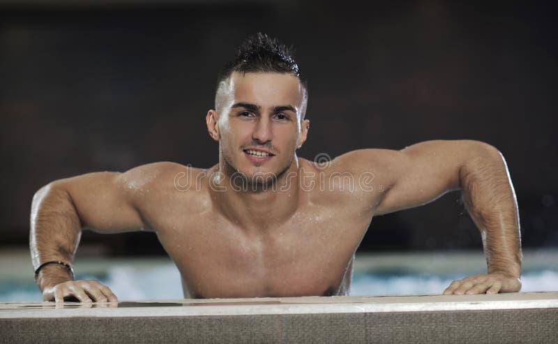 Macho man. Young healthy good looking macho man model athlete at hotel indoor pool stock image
