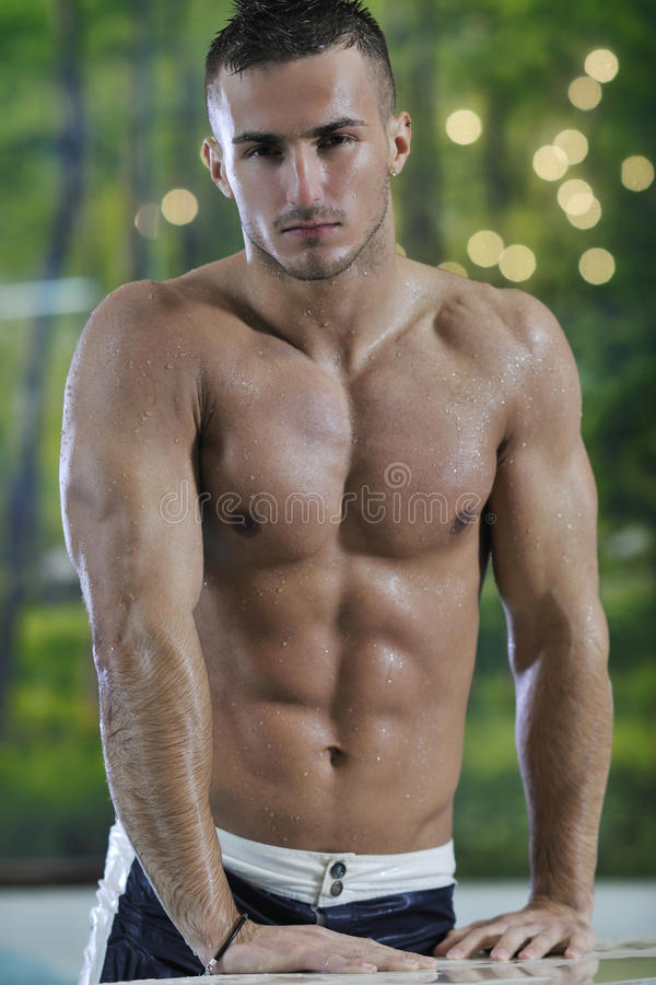 Macho man. Young healthy good looking macho man model athlete at hotel indoor pool stock images