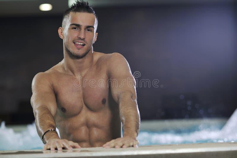 Macho man. Young healthy good looking macho man model athlete at hotel indoor pool stock photo