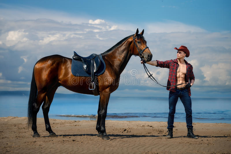 Macho man handsome cowboy and horse on the background of sky and water. Macho man handsome cowboy with amazing muscles and abs and horse are on the background stock photo