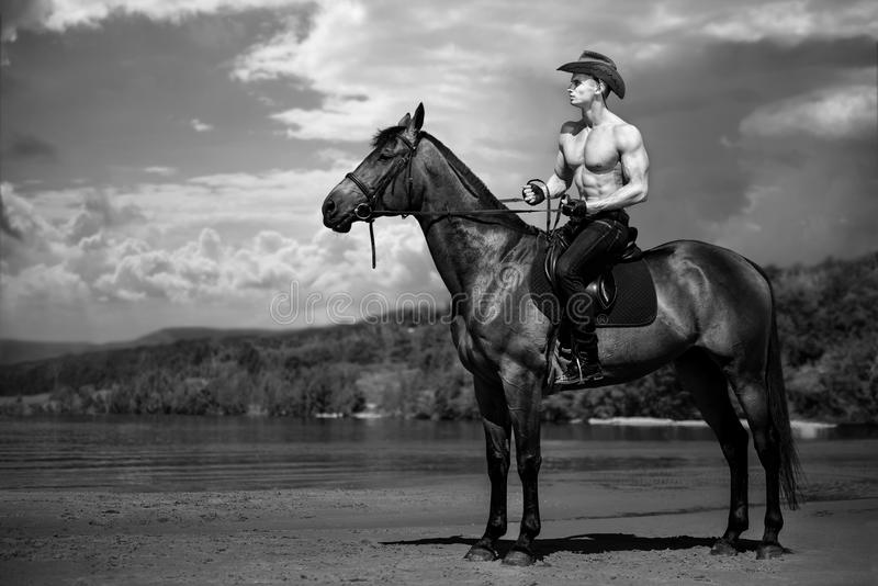 Macho man handsome cowboy riding on a horse on the background of sky and water. royalty free stock photos