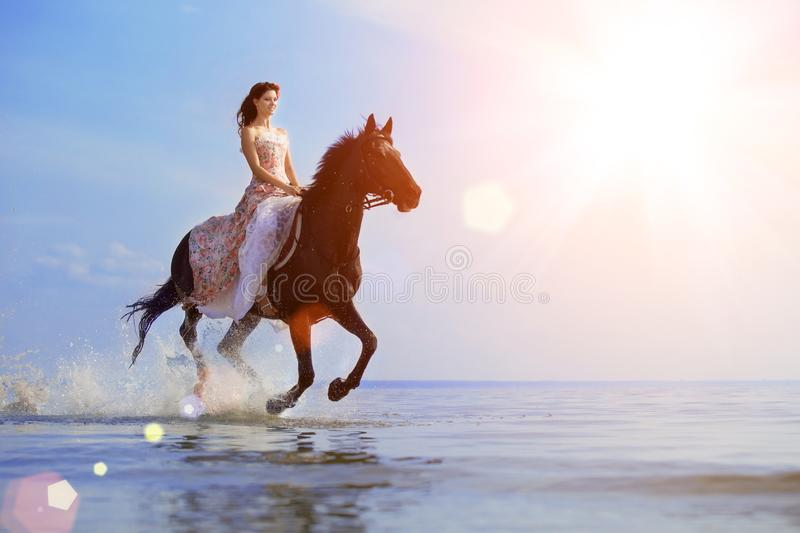Macho man and horse on the background of sky and water. Boy mode. L, cowboy on horseback on the beach by the sea at sunset. Men, backlit in sunshine. A positive royalty free stock images