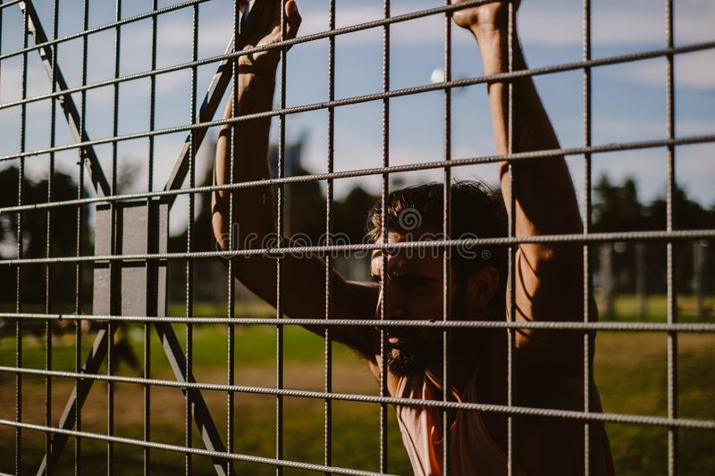 Macho man leaning on the fence royalty free stock image