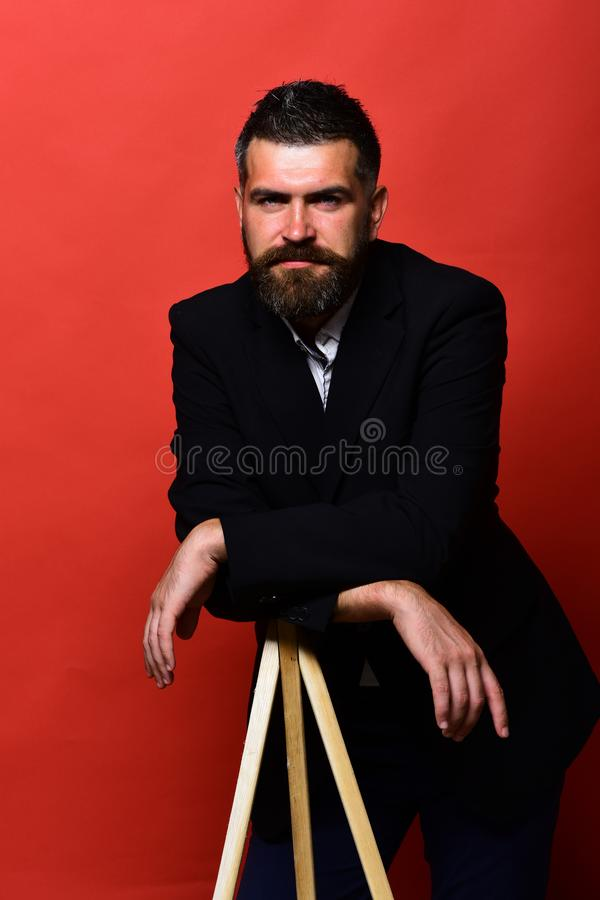 Macho man leans on photo tripod on red background stock image