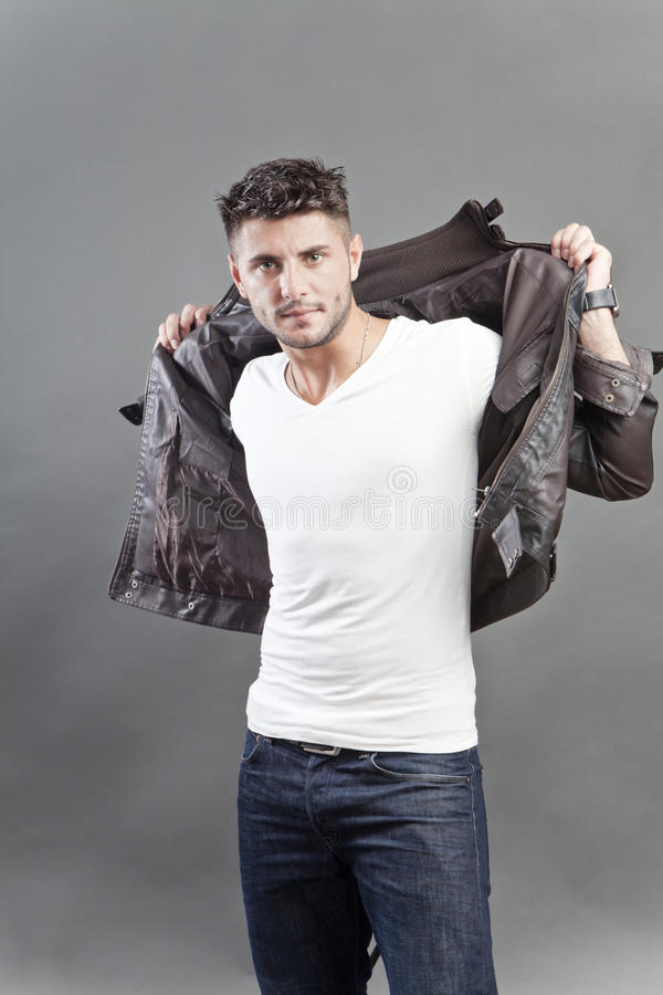 Macho man making an appearance. Macho man in studio portrait dressed in leather jacket making an appearance royalty free stock photo