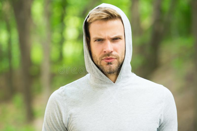 Macho man. man in hood. casual style. male fashion. unshaven guy outdoor. seriousness and masculinity. sportswear royalty free stock photography