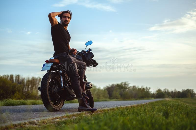 Macho man sitting on his bike and holding his hair. Macho man sitting on his bike in the middle of the road and holding his hair royalty free stock images