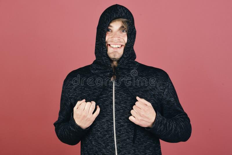 Macho med den lyckliga le framsidan binder huven stramt Grabb med borstet i mörk grå färg- och svarthoodie arkivfoton
