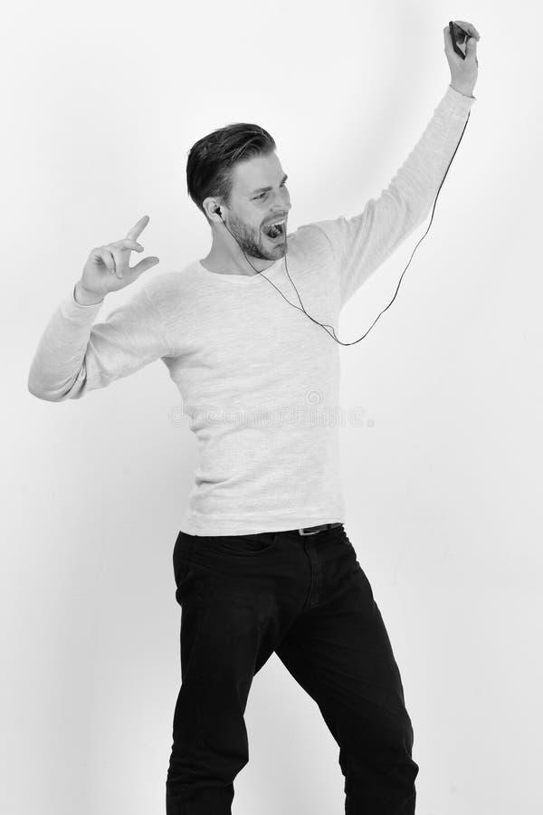 Macho med hörlurar och mobiltelefonen lyssnar till musik fotografering för bildbyråer