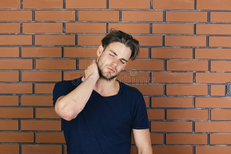 Macho med handen för lidandeframsidahåll på hals royaltyfri fotografi