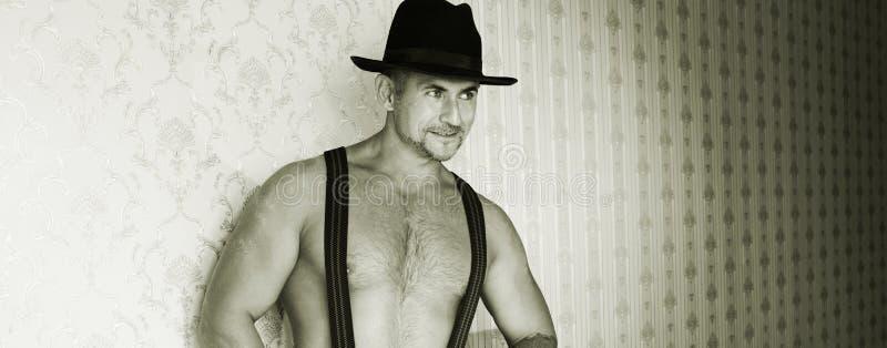 Macho muscular em um chapéu de feltro fotos de stock royalty free