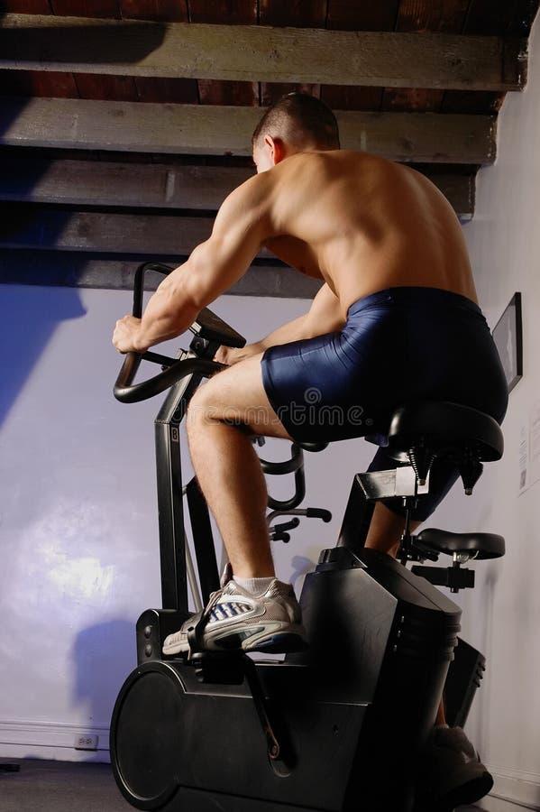 Macho na bicicleta de exercício fotografia de stock royalty free