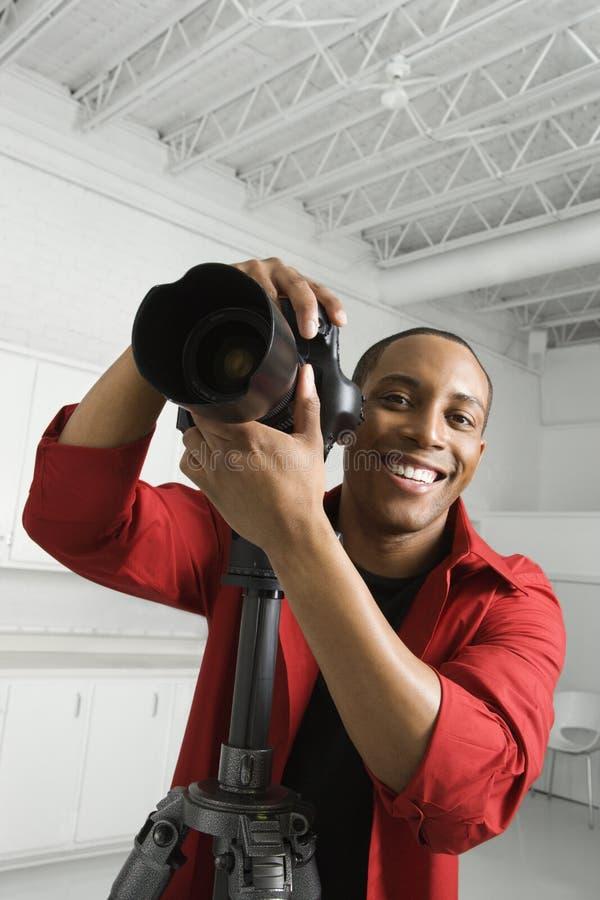Macho novo com a câmera no tripé. fotos de stock royalty free