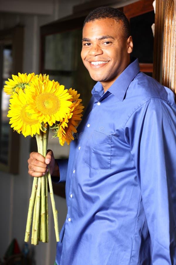 Macho novo do americano africano com girassóis foto de stock royalty free