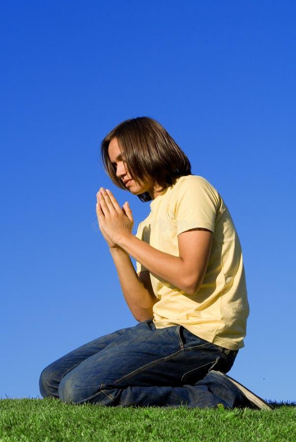 Macho novo que praying fotografia de stock