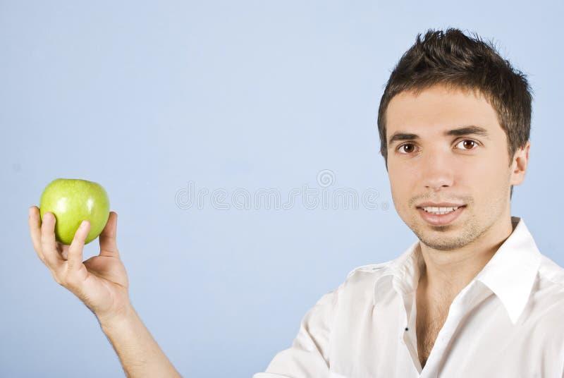 Macho novo que prende uma maçã verde fotografia de stock royalty free