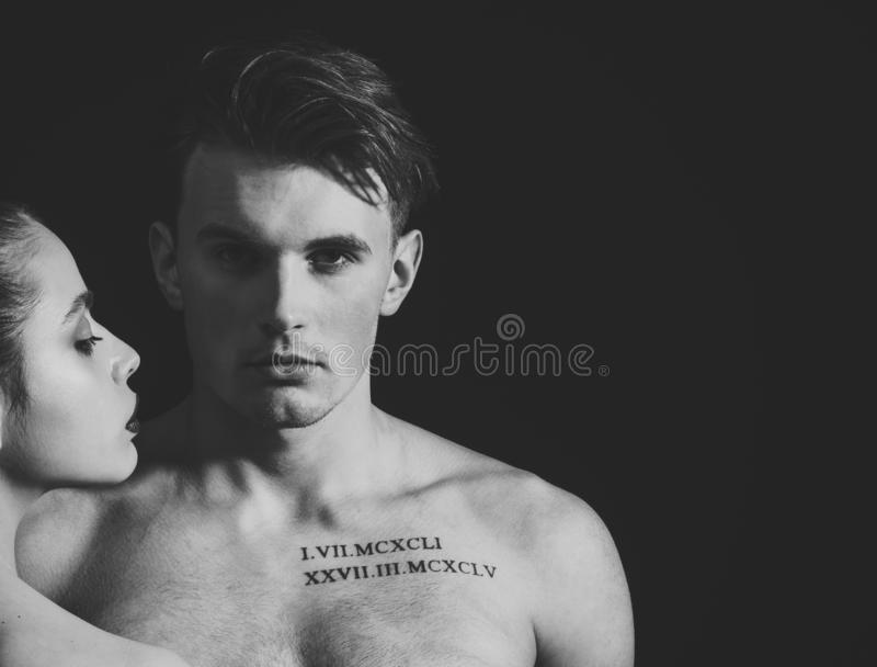 Macho on pensive face with muscular figure, enjoy female attention. Man with muscular torso, macho and female face, dark. Background. Pheromones, desire and royalty free stock photo