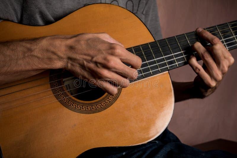 Macho que joga a guitarra acústica imagens de stock royalty free