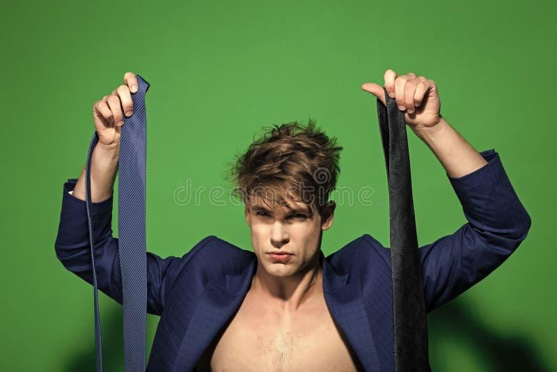 Macho scelga la cravatta in giacca blu senza camicia su fondo verde fotografie stock