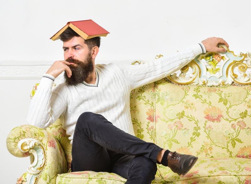 Macho senta-se com o livro aberto na cabeça, como o telhado Conceito aborrecido da literatura O homem com barba e bigode senta-se imagem de stock